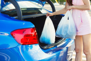 Cropped image of woman putting shopping bags inside trunk of her blue car