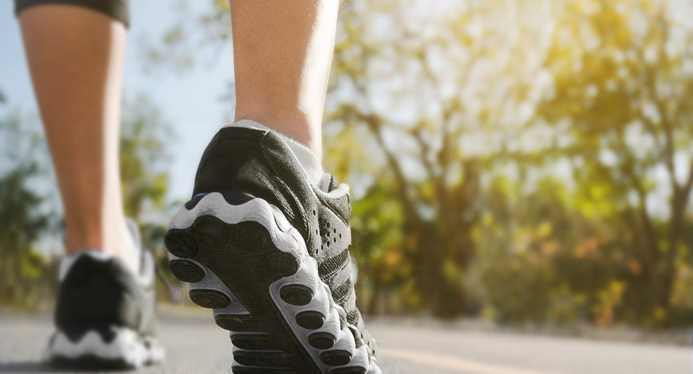 Athlete runner feet running on road closeup on shoe with nature background