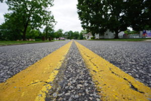 Double Yellow Lines That Vanish Into Distance as They Converge on Empty Road