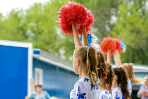 group of young girls cheerleader with red pom-poms