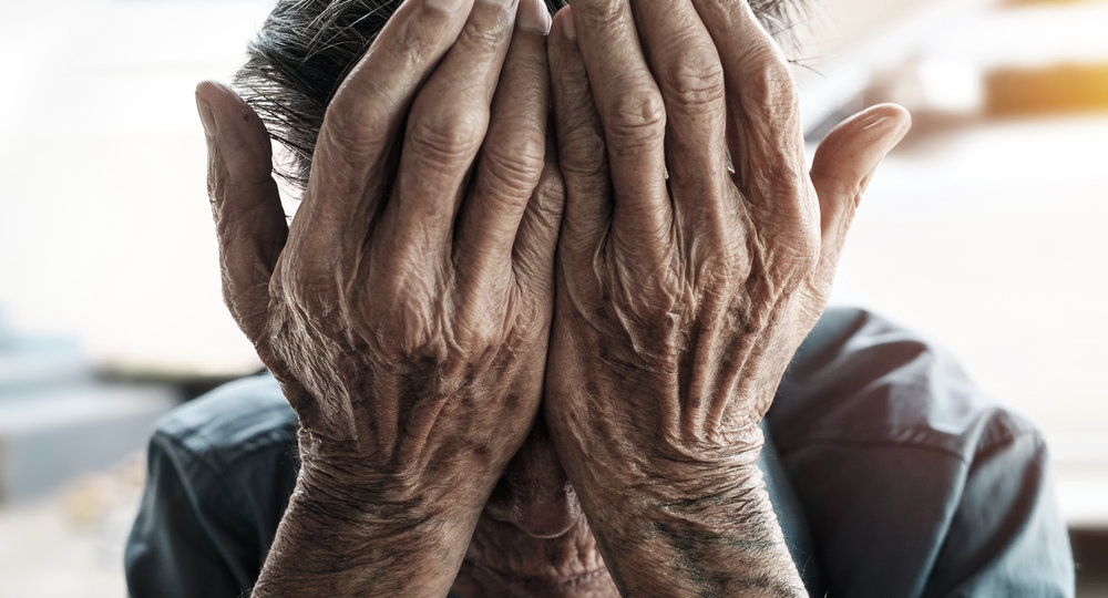 senior man covering his face with his hands