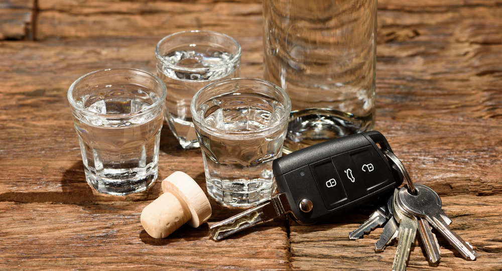 Shot glasses and a car key on an old wooden table